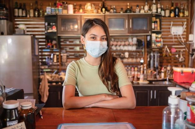 Aantrekkelijke jonge aziatische vrouwelijke ondernemer die een gezichtsmasker draagt dat staat om klanten te verwelkomen aan een houten toonbank in restaurant