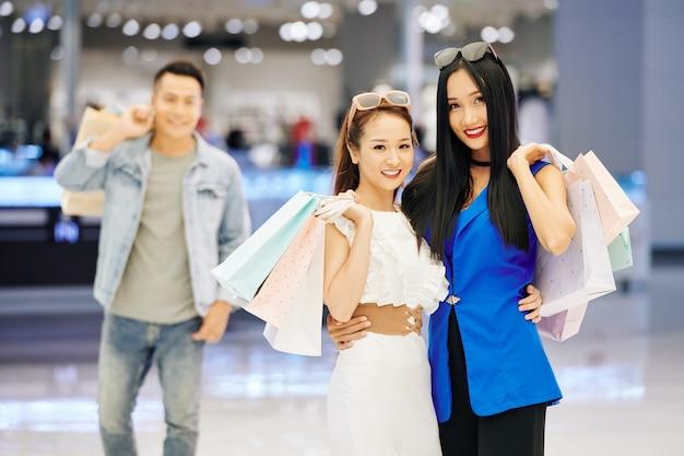 Aantrekkelijke jonge aziatische vrouwen met boodschappentassen die zich in winkelcomplex bevinden