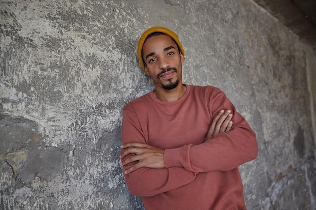 Aantrekkelijke jonge, bebaarde donkere man met bruine ogen die positief kijken en gevouwen handen op zijn borst houden, staande over betonnen muur in vrijetijdskleding