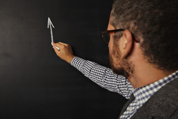 Aantrekkelijke jonge bebaarde leraar die een grafiek op het bord begint te tekenen