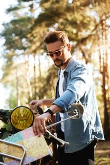 Aantrekkelijke jonge bebaarde man in de buurt van scooter kijken naar kaart