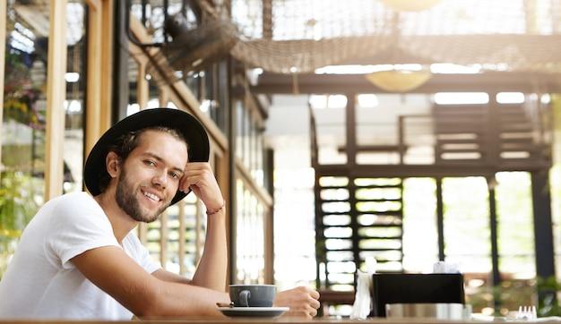 Aantrekkelijke jonge bebaarde man in trendy zwarte hoed op zoek met gelukkige glimlach, genieten van goede koffie en mooi weer terwijl u ontspant in café alleen tijdens het ontbijt