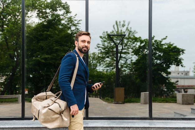 Aantrekkelijke jonge bebaarde man met een jas die buiten op straat loopt, een tas draagt, een mobiele telefoon vasthoudt