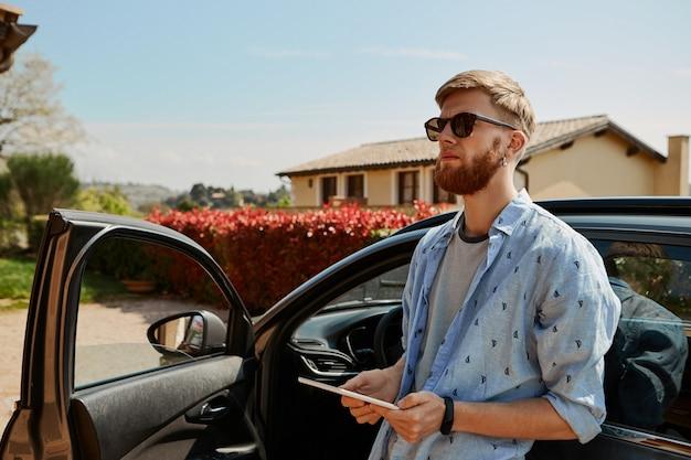 Aantrekkelijke jonge bebaarde mannelijke taxichauffeur in zonnebril die achterover op zijn auto leunt