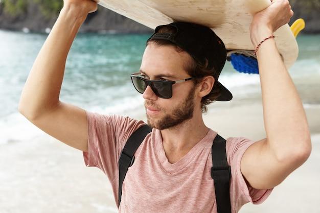 Aantrekkelijke jonge bebaarde surfer in tinten permanent op strand op de oceaan