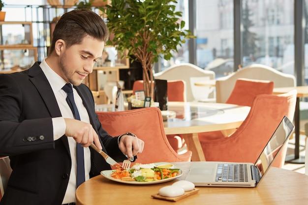 Aantrekkelijke jonge bedrijfsmens die ontbijt heeft in lokaal koffie