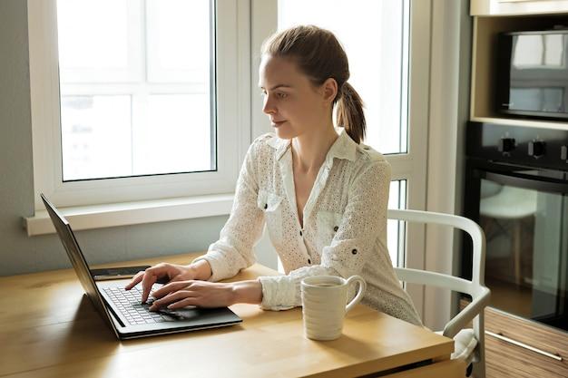 Aantrekkelijke jonge bedrijfsvrouw die met computerlaptop thuis aan houten lijst werkt