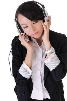 Aantrekkelijke jonge bedrijfsvrouw die van muziek geniet door mp3-speler en hoofdtelefoon.