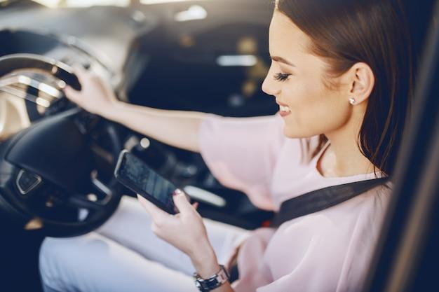 Aantrekkelijke jonge blanke brunette met brede glimlach en gekleed elegante rijdende auto en kijken naar slimme telefoon.