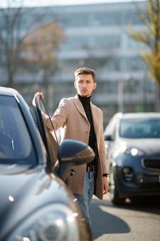 Aantrekkelijke jonge blanke man opent een autodeur, gekleed in beige jas in het centrum op een zonnige dag