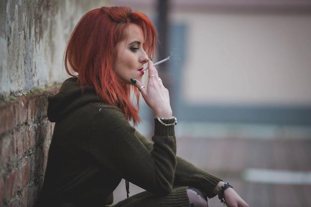 Aantrekkelijke jonge blanke vrouw in een groene jurk die rookt en poseert voor een oud gebouw