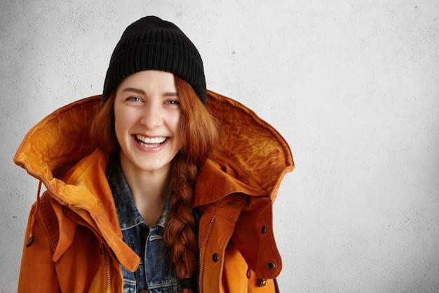 Aantrekkelijke jonge blanke vrouw met gemberhaar en gelukkige glimlach