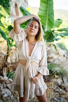 Aantrekkelijke jonge blanke vrouw staat in de buurt van bananenbomen in tropisch park