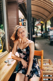 Aantrekkelijke jonge blanke vrouwenzitting in straatkoffie