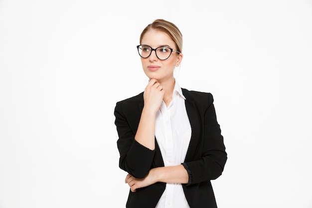 Aantrekkelijke jonge blonde bedrijfsvrouw in oogglazen die hand houden dichtbij kin en weg over wit kijken