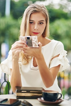 Aantrekkelijke jonge blonde vrouw die compacte spiegel bekijkt om haar samenstelling te controleren