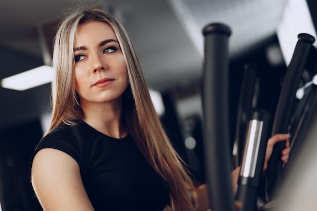 Aantrekkelijke jonge blonde vrouw die op cardio-trainingsapparatuur uitoefent
