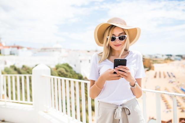 Aantrekkelijke jonge blonde vrouw typen op telefoon op terras met uitzicht op het strand