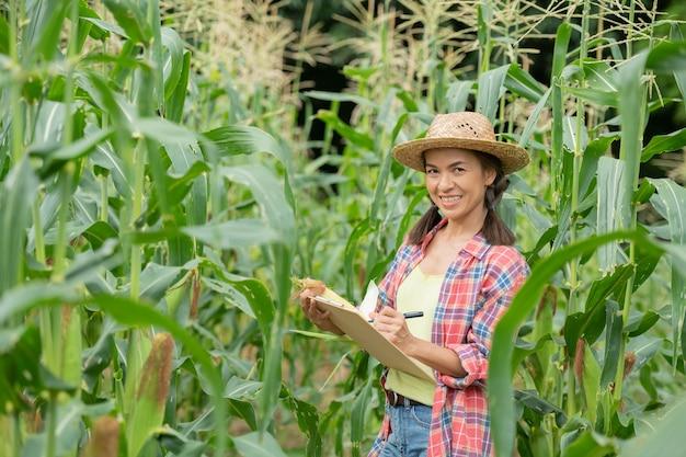 Aantrekkelijke jonge boer glimlachend staande in het maïsveld in het voorjaar