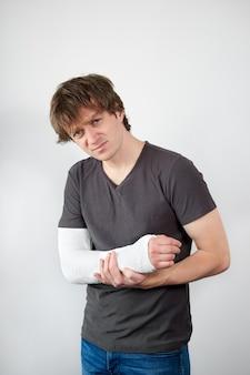 Aantrekkelijke jonge boos blanke man met gipsverband op zijn hand die lijdt aan pijn op een witte muur