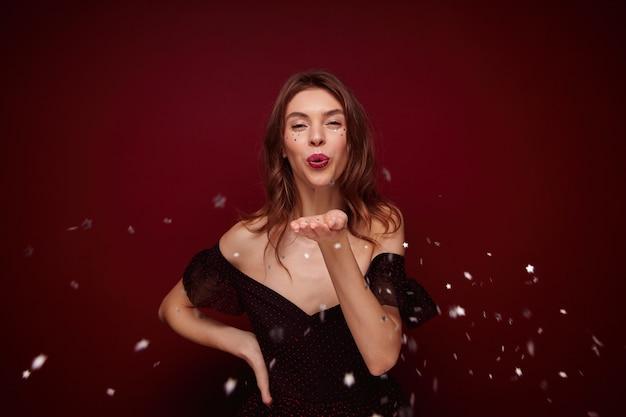 Aantrekkelijke jonge brunette dame met golvend kapsel feestelijke kleding dragen terwijl staande, met vrolijke momenten in haar leven tijdens nieuwjaarsfeest