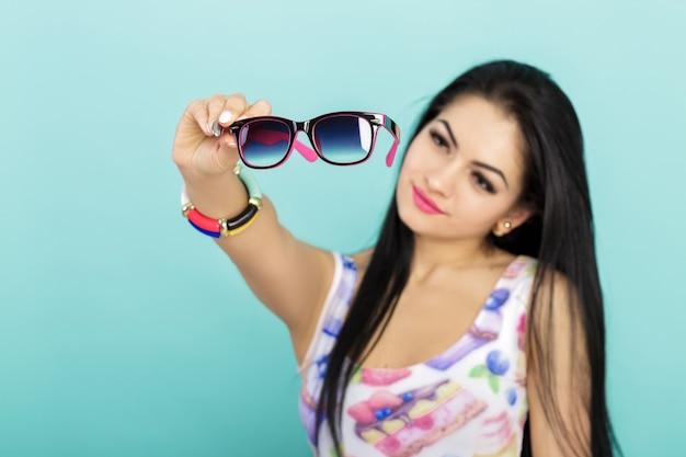Aantrekkelijke jonge brunette vrouw in roze tanktop met zonnebril op blauwe focus op bril