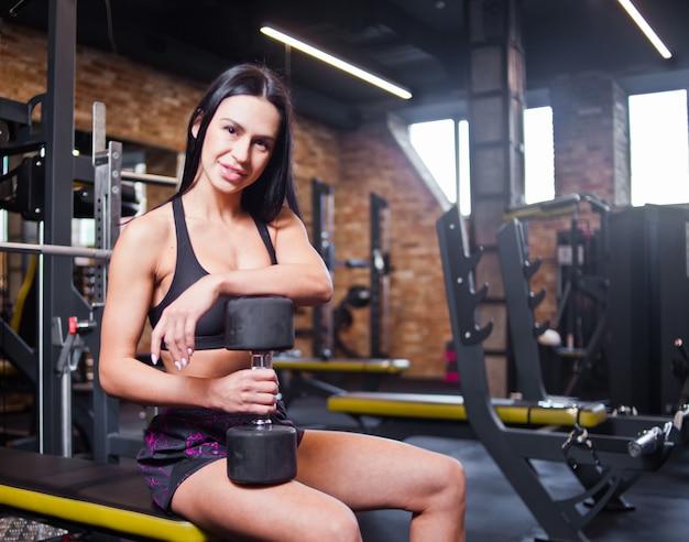 Aantrekkelijke jonge brunette vrouw in sportkleding met een halter in haar hand zittend op een bankje in de sportschool en glimlachen