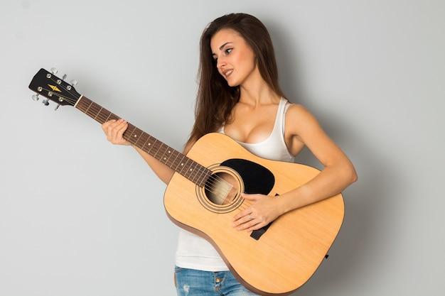 Aantrekkelijke jonge brunette vrouw met gitaar glimlachend in studio