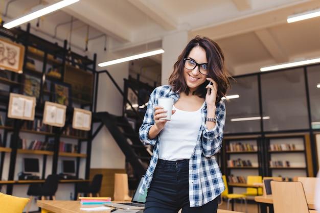 Aantrekkelijke jonge brunette vrouw met koffie praten over telefoon in bibliotheek. koffiepauze, universiteitsleven, modern werk, studeren, slimme student, goed werk.