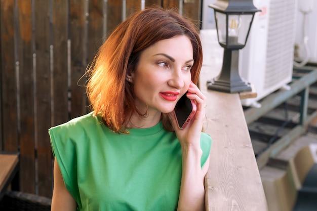 Aantrekkelijke jonge brunette vrouw praten op een mobiele telefoon op de open veranda van een stadscafé