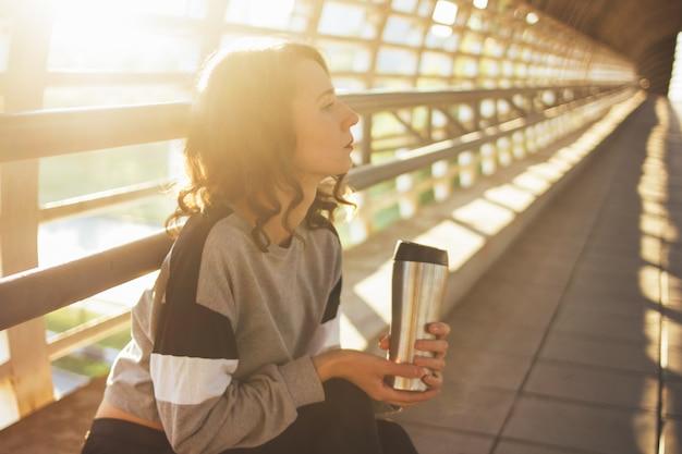 Aantrekkelijke jonge brunette vrouw straat danser turnster zitten en rust met thermo cup