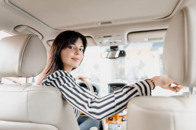 Aantrekkelijke jonge brunette vrouw zitten achter een stuur van een auto zitten en glimlachen op zoek naar een achterbank waar haar kinderen zitten