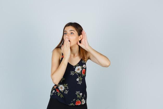 Aantrekkelijke jonge dame die de hand op de mond houdt terwijl ze een privégesprek in een blouse afluistert en er verrast uitziet, vooraanzicht.