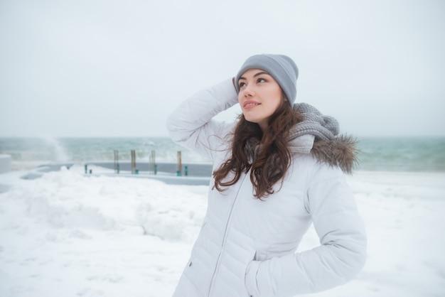 Aantrekkelijke jonge dame die hoed draagt die dichtbij strand loopt
