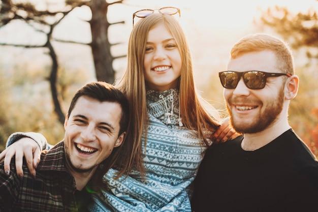 Aantrekkelijke jonge dame glimlachend en twee knappe mannen omarmen terwijl tijd doorbrengen in de natuur op zonnige dag samen. vrouw omhelst mannen in de natuur