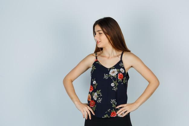 Aantrekkelijke jonge dame hand in hand op de taille terwijl ze opzij kijkt in blouse en er hoopvol uitziet. vooraanzicht.