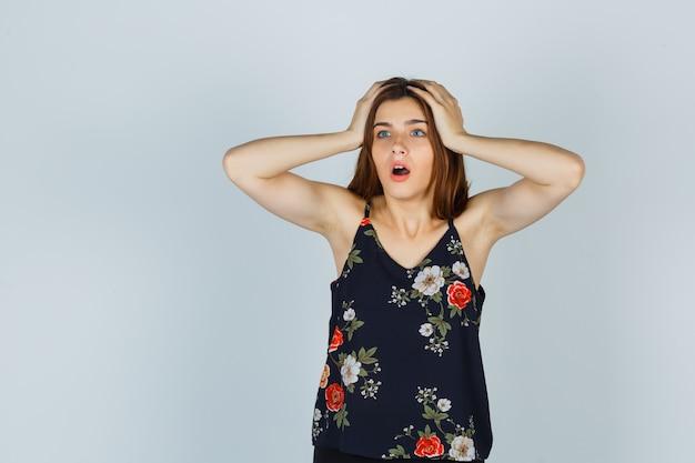Aantrekkelijke jonge dame hand in hand op het hoofd in blouse en kijkt verbaasd. vooraanzicht.