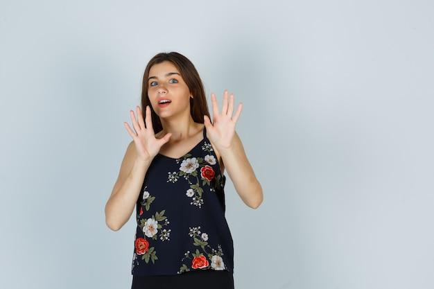 Aantrekkelijke jonge dame in blouse die een stopgebaar toont en er bang uitziet, vooraanzicht.