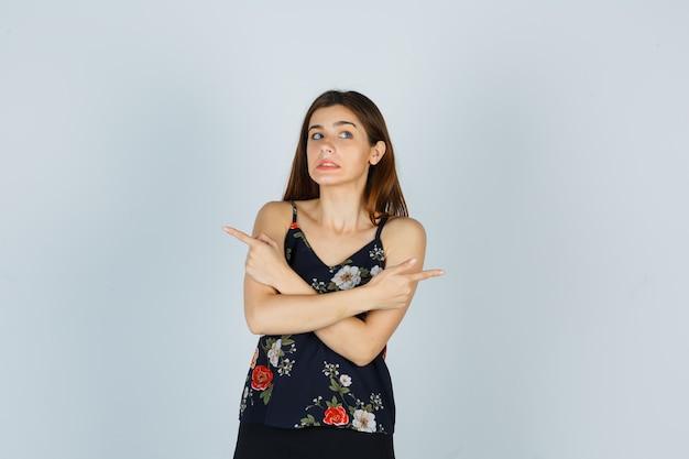 Aantrekkelijke jonge dame in blouse die naar de tegenovergestelde kanten wijst en verbijsterd kijkt, vooraanzicht.