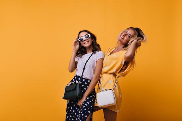 Aantrekkelijke jonge dames die samen dansen. indoor portret van vrolijke zusters in trendy kleding staande op geel.