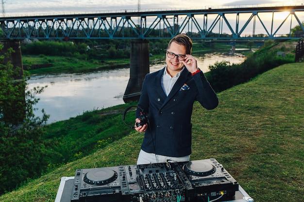 Aantrekkelijke jonge dj met hoofdtelefoons en mixer buiten in de zomer. brug, rivier en zonsondergang op de achtergrond