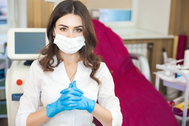 Aantrekkelijke jonge dokter. portret van vrouw die rubberhandschoenen en masker draagt.