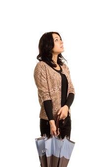 Aantrekkelijke jonge donkerbruine vrouw die een gesloten paraplu aan haar zijde houdt die omhoog kijkt
