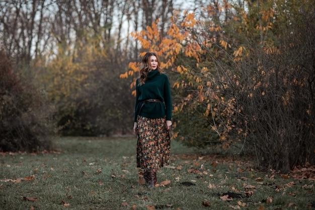 Aantrekkelijke jonge donkerbruine vrouw die in het de herfstpark loopt. kopieer ruimte.