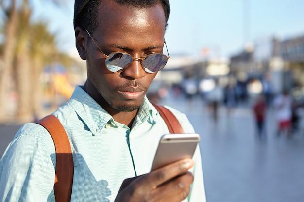 Aantrekkelijke jonge donkere mannelijke toerist met behulp van online navigatie-app op mobiele telefoon. modieuze zwarte man sms-bericht