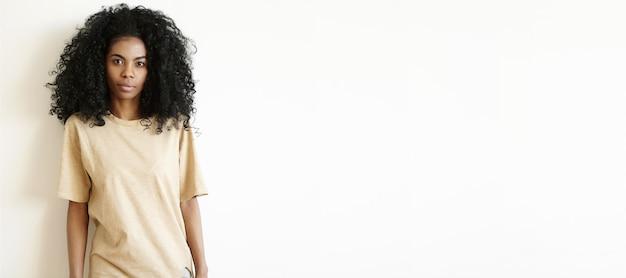 Aantrekkelijke jonge donkere vrouw met afro kapsel dragen oversized t-shirt kijken, met ernstige gezichtsuitdrukking. schattig afrikaans meisje gekleed nonchalant poseren binnenshuis op witte muur