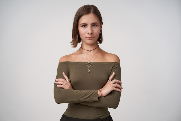 Aantrekkelijke jonge donkerharige dame met kort kapsel die haar handen gekruist houdt terwijl ze serieus naar de voorkant kijkt, staande over een witte muur in een olijfblouse
