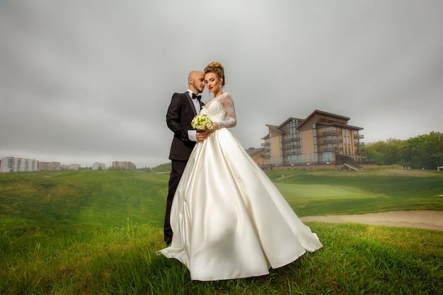 Aantrekkelijke jonge elegante merried paar buitenshuis knuffelen op een groen gras