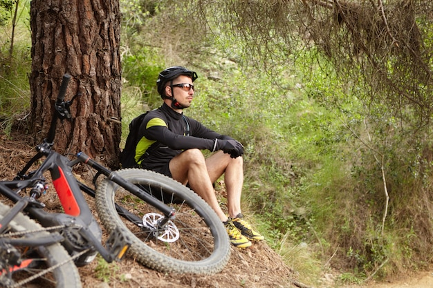 Aantrekkelijke jonge europese rijder in beschermende kleding zittend op de grond op boom, overweegt verbazingwekkende wilde natuur om hem heen terwijl hij rust na intensieve fietstraining in het bos op zijn e-bike