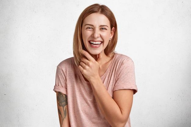 Aantrekkelijke jonge europese vrouw is erg blij, toont perfecte tanden, heeft plezier binnenshuis, verheugt zich na voorstel om vrolijk te zijn, heeft een getatoeëerde hand, geïsoleerd over een witte betonnen muur. geluk concept